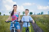 Mother and son riding bicycle in the field