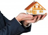 Businessman holding miniature house model on white background