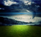 Digitally generated tornado over city and moutains