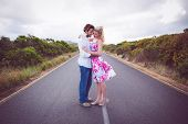 Cute couple standing on the road hugging on a dull day