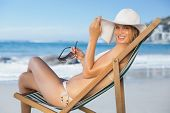 Smiling woman relaxing in deck chair on the beach on a sunny day
