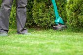 picture of trimmers  - man mowing lawn with green grass trimmer - JPG