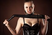 image of sadomasochism  - angry mistress with a whip in hands - JPG