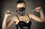 stock photo of sadist  - woman in a mask with a chain in hands - JPG