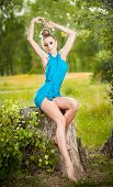 Portrait of young beautiful blonde woman wearing blue dress posing on a stump in a green forest