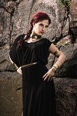 foto of tunic  - Beautiful makeup girl wearing black tunic and an antique jewels rocky wall on background - JPG
