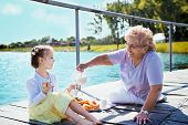 stock photo of granddaughters  - Grandmother with granddaughter eating breakfast on the lake - JPG