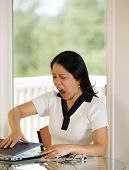 stock photo of slam  - mature woman angrily slamming her laptop shut while working from home with blurred out daylight coming in from window in background - JPG