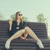 image of teen smoking  - Hipster girl smoke in park - JPG
