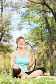 Happy woman holding a hula hoop seated in the park