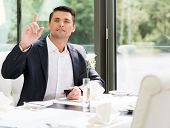 Handsome man with mobile phone in restaurant asking for waiter