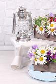 Beautiful flowers in crates with kerosene lamp on wooden stand on light background