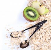 Apple, kiwi fruit with oatmeal and vintage spoon isolated on white