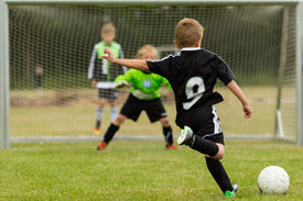 stock photo of football pitch  - Goalkeeper and penalty kicker in the midst of a penalty kick during a youth soccer match - JPG