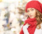 happiness, winter holidays, christmas and people concept - young woman in red hat and scarf over lights background
