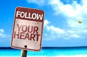 Follow Your Heart sign with a beach on background
