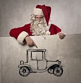 Santa Claus pointing out the picture of an old-fashioned car