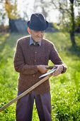 stock photo of scythe  - Old caucasian farmer sharpening his scythe to mow the land traditionally - JPG