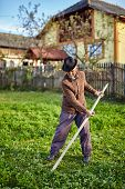 foto of scythe  - Senior farmer mowing the grass with a scythe in the backyard of his house - JPG