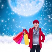 Blonde in winter clothes holding shopping bags against blue background with vignette