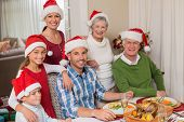 Happy extended family in santa hat looking at camera at home in the living room