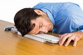 Businessman sleeping with his head on the keyboard on white background