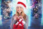 Festive blonde holding christmas gift and bag against glittering screen in urban setting