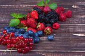 Strawberries blueberries blackberries raspberries and currant on wooden background