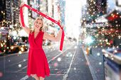 Stylish blonde in red dress holding scarf against blurry new york street