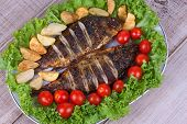 Whole grilled fish carp served with potatoes tomatoes cherry and salad
