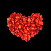 Cornel berries as a heart shape isolated on black background
