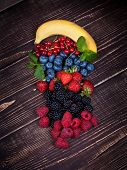 Strawberries blueberries blackberries raspberries currant and banana on wooden background