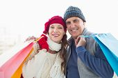 Happy couple in warm clothing with shopping bags on white background