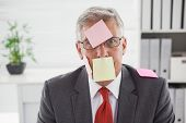 Confused businessman with sticky notes on head in his office