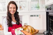 Smiling woman holding roast turkey at home in the kitchen