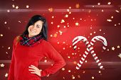 Portrait of a pretty brunette posing against christmas candy canes on red
