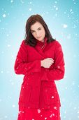 Pretty brunette in red coat posing against blue background with vignette