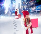 Pretty blonde showing red poster against santa delivering gifts in city