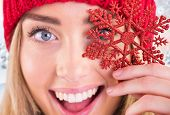 Happy blonde holding red snowflake against snowy landscape with fir trees