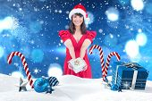 Festive brunette giving a gift against christmas scene with gifts and candy canes