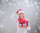 Confused blonde in santa hat holding gifts against grey vignette
