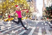 Festive blonde skipping and smiling at camera against blurry new york street