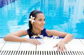Beautiful woman with frangipani flower in hair, relaxing in the pool in full blue dress