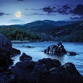 Lake Shore With Stones Near Forest On Mountain At Night