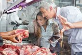 Mature couple buying fresh meat at butchery