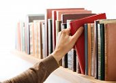 Hand taking book from the shelf.