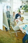 Team meeting in conference room of office with man at whiteboard