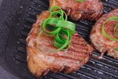 roast bloody beef fillet steaks on black teflon grill plate with green leaves  isolated on white background