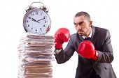Angry businessman hitting clock isolated on white