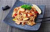 pic of chinese parsley  - Chinese noodles with vegetables and seafood on plate on bamboo mat background - JPG